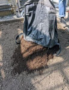 And then the bag is hand carried into the greenhouse and emptied onto each bed. The compost mix is very dark and fine. It is a blend of composted manure and plant materials.