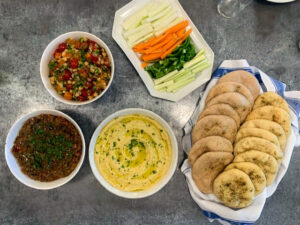The pita bread was served with chickpeas, cherry tomatoes, sun-gold tomatoes, cucumbers, green peppers, parsley, lemon juice, olive oil, a classic hummus tehina, and a twice cooked eggplant dip.
