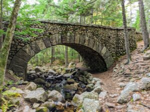 Located south of the Jordan Pond House along the picturesque Jordan Stream is the Cobblestone bridge which was built in 1917. It is 150 feet in length and 21 feet tall. It is the only one of Rockefeller's 16 bridges that is made entirely of cobblestones. This bridge is located at the top end of Little Long Pond.