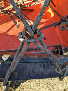 The harrow has a rigid frame that holds metal chain links.