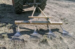 Here, Chhiring hooks up the rakes to the back of the tractor and goes over the land to mix up the seed with the soil.