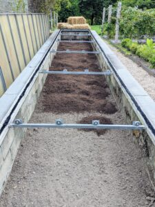 This long cold frame is located between the main greenhouse and my perennial flower garden, where it can be closely monitored during the season. Historically, cold frames were built as greenhouse extensions tucked against the outer walls with southern exposure outside Victorian glasshouses. Here, it is being given a fresh layer of compost.