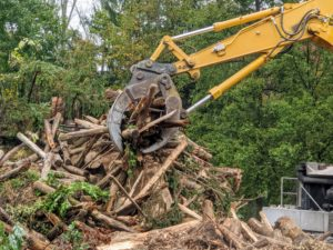 Dan operates much of the machinery during the time it is at the farm. He begins with the excavator grabbing large amounts of logs and brush.