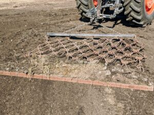 The harrow is supported at the front by a rigid towing-bar.