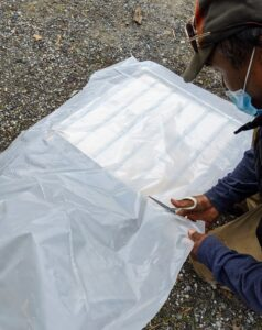 Next, he cuts a piece of weather proofing plastic just a bit larger than the shutter's dimensions.