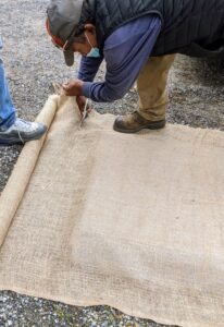 Then he cuts a pice of burlap the same size as the plastic sheeting.