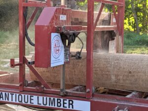 The saw works its way down the log. After each cut, the machine is stopped so the cut board can be removed.
