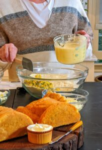 The flour, cornmeal, salt, pepper, sugar, baking powder, baking soda, and cheese are all combined in a large bowl.