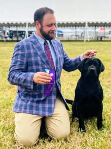 "Recently, Tim was in Virginia showing Kima trying to get her AKC Championship points. In this photo, Kima had just won ""Winners Bitch"" and ""Best of Winners."" ""Best of Winners"" is awarded to either the ""Winners Dog"" or ""Winners Bitch."" It denotes the best dog out of all the regular class entries (non-champions). Doesn't Kima look beautiful here? It is nice to have great handlers that you trust with your animals. Tim and Megan always do a great job with my dogs. Thanks, guys."