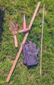 On a sunny, warm day, Hannah prepared all her tools for planting - a hand cultivating fork, a dibber, which is a pointed wooden stick for making holes in the ground so that seeds, seedlings or small bulbs can be planted, a pair of gloves, and a ruler.