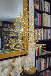 We call this the Lit Ball Twig Tree. These champagne colored trees come in 24 inch or 36 inch sizes. Each of the branches is decorated with 70 warm white LED lights. They can be used alone or in a grouping on your table or mantel. Plus it has a remote to control brightness, light functions and timed sessions.