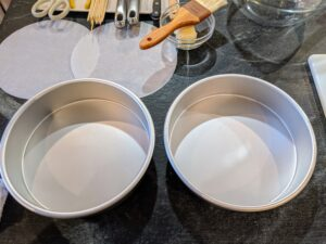 The recipe calls for two eight-inch round cake pans brushed with butter and lined with parchment paper.