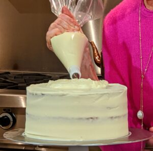 The cake is refrigerated for about 30-minutes and then ready for the final coat of frosting. I am holding a pastry bag fitted with a Wilton #104 petal tip. Starting from the center of the top of the cake, I pipe the entire cake while slowly turning it on the rotating cake stand. This creates a swirl effect.