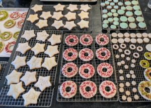 These cookies were just decorated and are ready to be displayed. In the center, crushed freeze-dried raspberries and pink peppercorns on icing-filled sugar cookies.