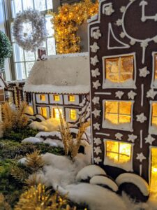 The entire village scene includes outdoor elements as well - gingerbread boxwood and trees covered in snow.