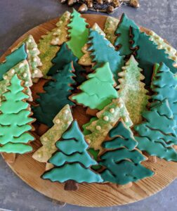 Green royal icing and sanding sugar were applied in sections to add texture to these gingerbread trees.