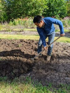Next, Pasang turns the soil, removing any leftover pieces of debris. He does this along the entire bed, turning it at least six to eight inches deep.