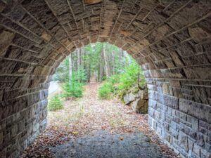 Cheryl loves to hike the many carriage roads and trails around Acadia National Park. She especially likes to visit the many stone bridges. This is a view through one of three arches of the Stanley Brook Bridge. As the last of Rockefeller's classic carriage-road bridges built, Stanley Brook Bridge is also one of the most magnificent, welcoming visitors into Acadia National Park. Each of its three arches has a purpose: automobile traffic goes under the large middle arch, the Seaside Path hiking trail goes under the smaller west arch, and Stanley Brook flows under the eastern arch.