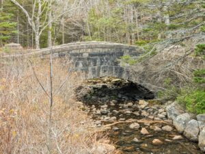 """And this is the Jordan Pond Dam Bridge. Built in 1920, the Jordan Pond Dam Bridge leads visitors from the Jordan Pond House out to the surrounding carriage roads. Unfortunately, this bridge is often unnoticed by visitors since Jordan Pond and the """"Bubbles"""" in the distance are the main attractions of the area."""