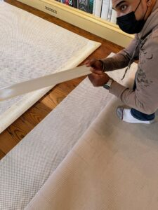 Because this room is large, two pieces of padding are needed to secure the carpet. Tape is used to connect the two pieces together, but don't worry, the tape never touches the floor.