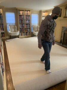 The rug is now rolled into place over the padding. The rug pad should stay completely flat to avoid any bunching that will cause bumps in the rug. The rug edges are also bound with cotton in the same color.