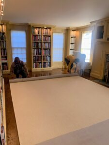 Once the carpet is positioned perfectly, it is rolled back to the other side, so the padding can be put down. With the carpet completely centered in the room, it will be easier to roll it back into place over the padding.
