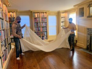Here, the team places the padding on the floor. Many rug pads are created from naturally non-slip materials to help anchor the pad to the floor and keep the rug stable.
