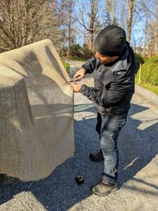 Next, Phurba cuts the burlap fabric to fit. When we can, we reuse burlap from seasons past, but some of the smaller pieces get new burlap every year. Burlap is available in giant rolls of 40-inches or 60-inches wide.