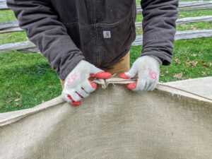 For another section, Chhiring has to make a new cover, so he sews the long sections together by hand – five lengths of burlap for each side. Chhiring has excellent sewing skills – I've taught everyone on the outdoor grounds crew how to sew.