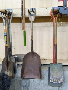 We keep like items together, so we always know where to find them and how many we have in supply. Here are some of the short-handled spades. Do you know the difference between a shovel and a spade? Shovels are broad-bottomed tools for moving loose materials, while spades tend to have a flat bottom edge for digging.