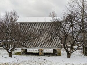 The snow has now covered the roof of the old corn crib.