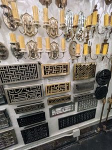 Here are more sconces - these are interior silver-plated sconces. Underneath are reproduction heating grates for both floor mount and wall mount. If a customer is looking for large quantities of an item that's in short supply, Liz manufactures and stocks those too.