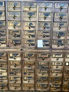 The key is to stay organized. Here, Liz categorizes bolts, fasteners, and locks in an old library library card catalog cabinet - every drawers is labeled with the item and the material.