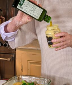 """Another classic """"Good Thing"""" is the no-waste salad dressing. It's always a challenge to get the last bit of mustard out of the jar - instead, just use the jar itself to make a delicious vinaigrette. Here I am pouring some olive oil into the jar already infused with fresh herbs."""