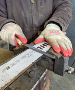 He files the sides of the rails to remove any metal burs caused by the chainsaw teeth.