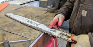 A chain on a chainsaw at a usable tension should have no visible slack. When it is lifted, it should have only about an eighth of an inch of give and snap back when released.