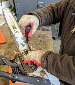 Chhiring uses a regular screwdriver to adjust the tension screws. He makes sure the chain is tight, but still able to move around the saw with little effort.