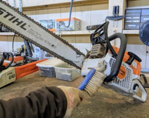 Chhiring brushes any dust or debris out from all the parts of the chainsaw.