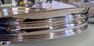Here is the side of another tray – not a trace of tarnish. With regular cleaning, the silver returns to its original luster very quickly. Polishing silver three or four times a year is generally sufficient to keep it in good condition. And, never place any silver in the dishwasher. The detergents' aggressive chemicals, combined with the washer's high cleaning temperature, will eventually turn it grey or white, with a dull, non-reflective surface.