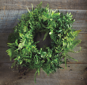 Houseplants don't always need to live in pots! This living wreath, covered in sphagnum moss and a variety of ferns, is an innovative way to spruce up a front door or any wall.