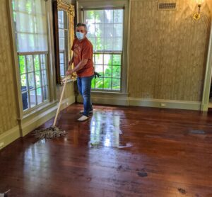 The first step was to change the carpets. The old carpeting was removed, and the floors were cleaned of any dust and stuck on old padding. Here is Fernando mopping the wood floors.