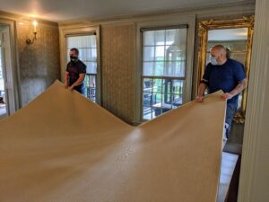 Here, the team adjusts the carpet, so it is completely centered in the room. Because the carpet is cut slightly smaller than the space to expose the wood floors, the area between the carpet edges and the walls is about four-and-a-half inches along every side.