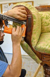 A pneumatic staple gun is used to attach the fabric to the piece.