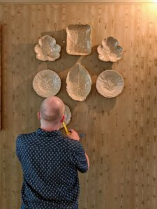 Each plate is carefully hung and measured in the same way it was arranged on the floor.