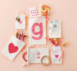 If you and your children are still making Valentines, use a stencil and some paint to embellish muslin bags to fill with treats. For something more custom made, cut the desired shape out of freezer paper, run the iron over it to keep it in place, and paint.