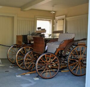 """When guests visit, I love to take them down to the Carriage House so they could see the beautiful horse carriages I keep inside. These """"sporty"""" open carriages were popular in the late 18th to early 19th centuries. They typically had minimal bodies and four extravagant wheels over open seating."""