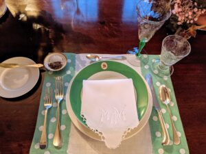 "Each place setting had a whimsical polka-dotted placemat. The green china plates are monogrammed with an ""S"" while the crisp white linen napkins show embroidered ""M"" letters."
