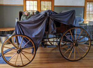 These carriages have four wheels instead of two. The sides are made of quarter-cut oak, with panels and moldings cut out of the solid wood.