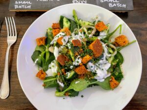 This local spinach salad includes asparagus, cucumbers, shallots, cornbread croutons, and a lemon-yogurt dressing.