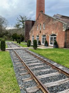 These were original train tracks built by Colonel E.H. Taylor to deliver visitors, coal, and charred bourbon barrels to buyers. The tracks were uncovered during renovation and incorporated into the design.